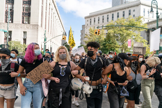 Demonstrators wearing protective masks march toward Jacob K. Javits Federal Building  during an Abolish I.C.E. protest