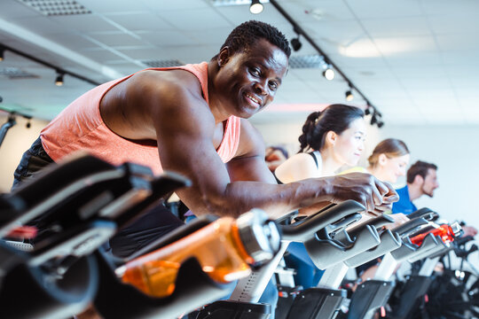 African man and friends on fitness bike in gym