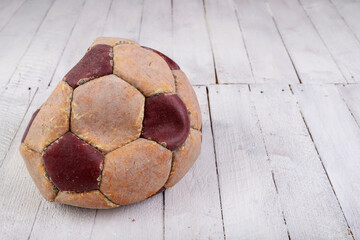 Old leather soccer ball on the white table. Accessories for the game of football.