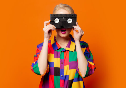 Style blonde in 90s clothes with VHS cassette