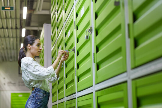 Waist up side view portrait of beautiful young woman opening padlock on door of self storage unit , copy space