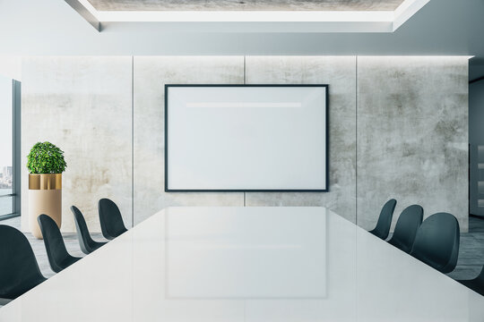 Meeting interior with long conference table and  projector screen on wall.