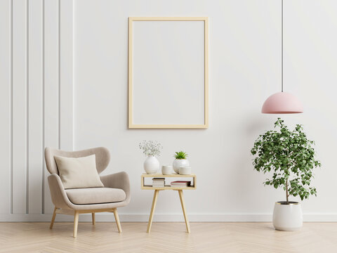 Poster mockup with vertical frames on empty white wall in living room interior with blue velvet armchair.