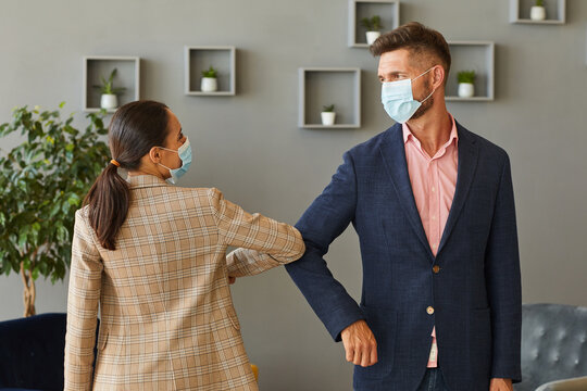 Waist up portrait of two successful business people wearing masks and bumping elbows as contactless greeting in post pandemic office