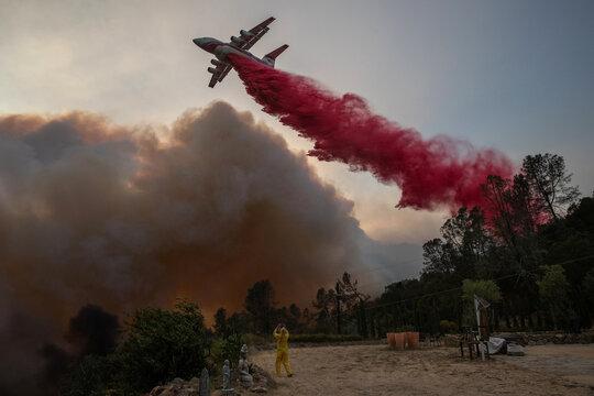 A woman photographs an airplane as it drops red fire retardant on the Glass Fire at an vinyard in Deer Park, California