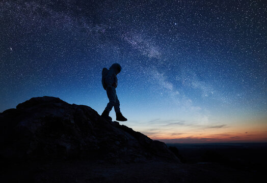 Full length of astronaut walking down the mountain under beautiful night sky with stars. Silhouette of cosmonaut in space suit exploring new planet. Concept of space travel, galaxy and human in cosmos