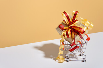 Shopping cart with gift box on beige gray background. Gifts wrapped in kraft paper with ribbon and bow. Holiday Shopping concept
