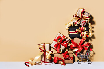Shopping cart with gift boxes on beige gray background. Gifts wrapped in kraft paper with ribbon and bow. Holiday Shopping concept