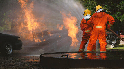 Firefighter fighting with flame using fire hose chemical water foam spray engine. Fireman wear hard hat, body safe suit uniform for protection. Rescue training in fire fighting extinguisher
