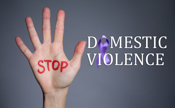 Female hand with text STOP DOMESTIC VIOLENCE on grey background