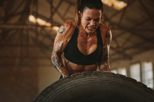 Strong woman performing tyre flipping workout