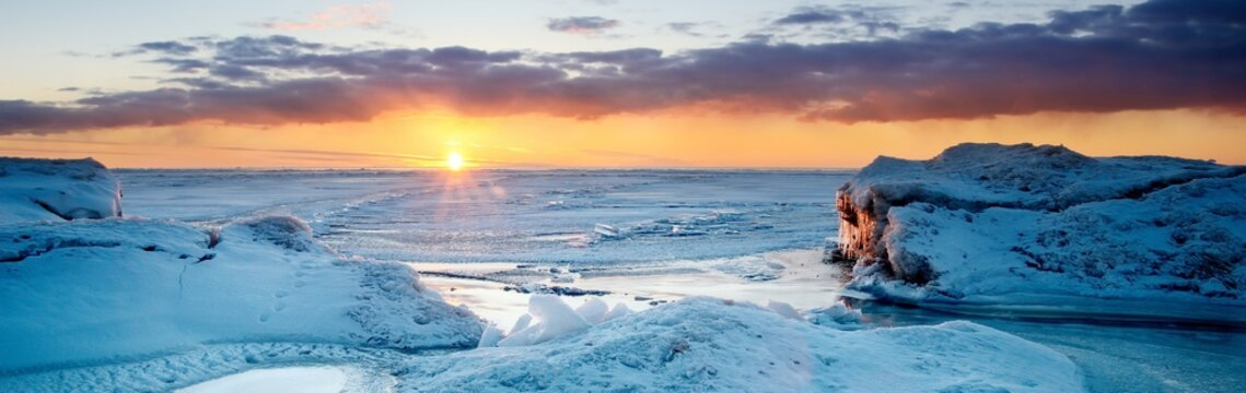 Picturesque panoramic scenery of the snowy Baltic sea shore at sunset,ice fragments close-up. Breathtaking view. Winter seascape. Pure nature, seasons, climate change