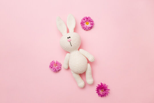 Knitted rabbit amigurumi with flowers chrysanthemums isolated on a pink background. Baby background. Copy space, top view
