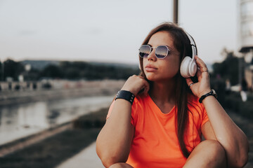 Photo sur Plexiglas Magasin de musique Young girl listening to music using headphones, teenager with sun glasses enjoying music in a park, girl with sunglasses and head phones