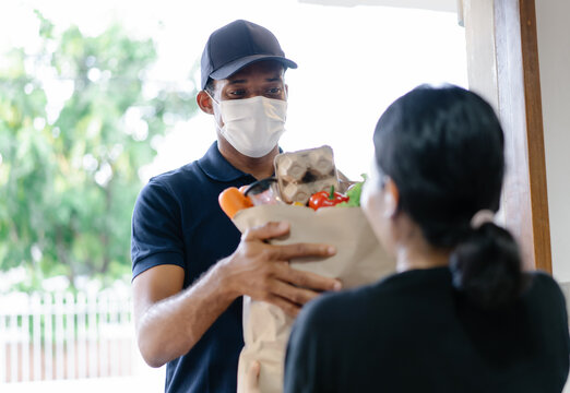 African American delivery man with medical mask delivering food to a woman at home.Online shopping and Express delivery. Under quarantine, disease outbreak, coronavirus covid-19 pandemic.