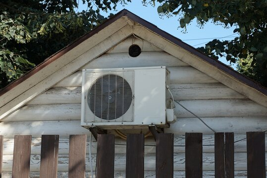 one gray metal air conditioner on a wooden attic wall behind a brown fence outside
