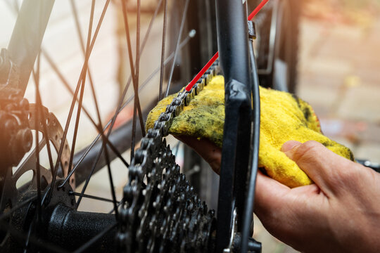 bicycle maintenance and repair - cleaning and oiling mountain bike chain and gear with oil spray
