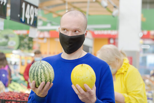 Male in a black medical mask stands in a supermarket. He has a melon and a watermelon in his hands, the man can choose what to buy. Background, you can see products and people in protective masks.