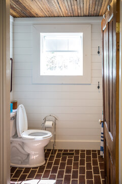Small and compact bathroom shower stall in a small farmhouse decor inspired cabin with a blue striped shower curtain, hooks on the wall and a rustic wood plank ceiling
