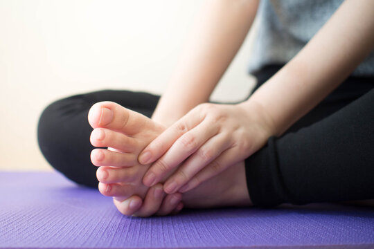 Foot pain - Young female massaging her painful foot after sport workout indoors while sitting on stretching mat. Health care concept. Close up.