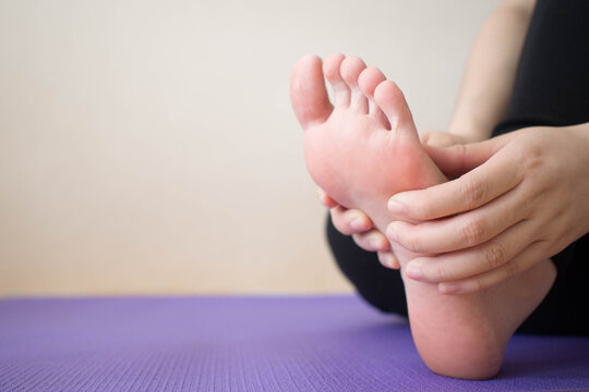 Foot pain - Young female massaging her painful foot after sport workout indoors while sitting on stretching mat. Health care concept. Close up. Copy space.