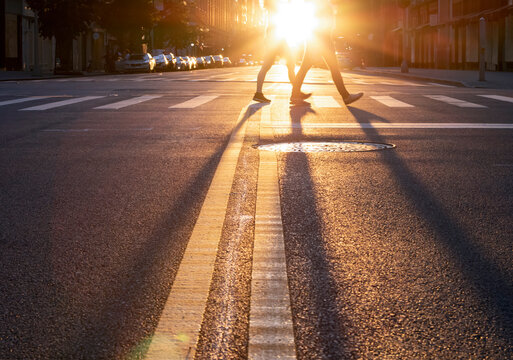Man and woman walking across the street in New York City with the light of sunset casting long shadows in the intersection
