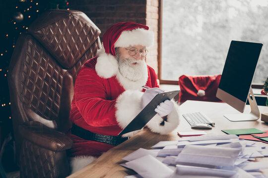 Photo of hard-working grey hair santa claus prepare x-mas christmas sit table write clip board organize wish list letters order wear cap headwear in advent spirit lights house indoors
