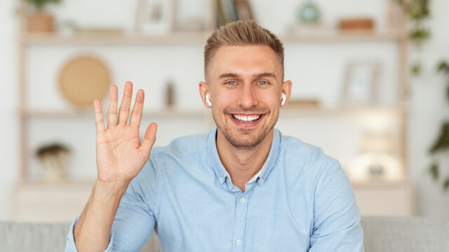 Guy sitting at home on the sofa and waving