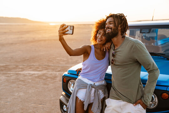 Image of african american couple taking selfie on cellphone in desert