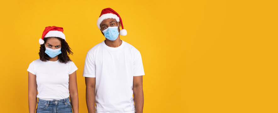 Disappointed Black Couple Wearing Masks And Santa Hats, Yellow Background