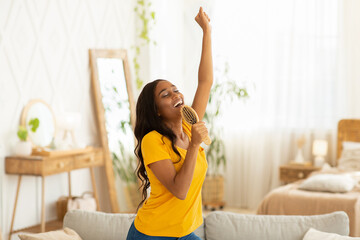 Cheerful black woman with hairbrush as mic singing her favorite song and dancing at home
