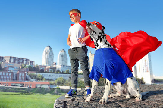 Boy and his dog wearing superhero costumes
