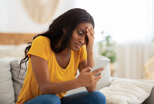 Unhappy African American lady looking at her smartphone with disgust indoors, copy space