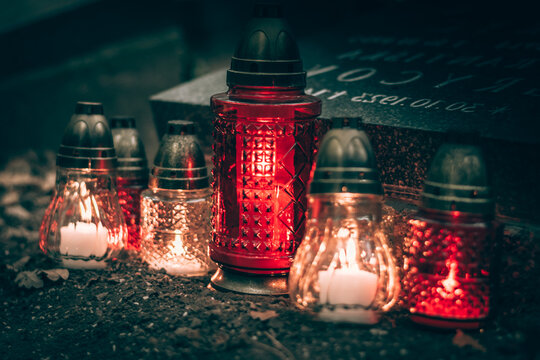 All Saints Day concept, burning candles in lanterns in the cemetery with night atmosphere