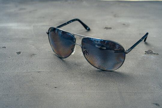 New dark aviator glasses on grey concrete background