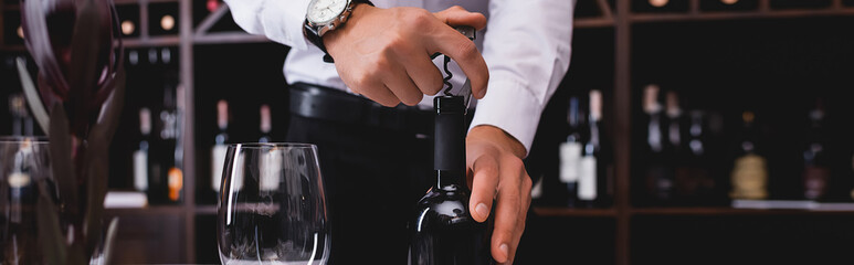 Panoramic shot of sommelier opening bottle of wine near glass of wine
