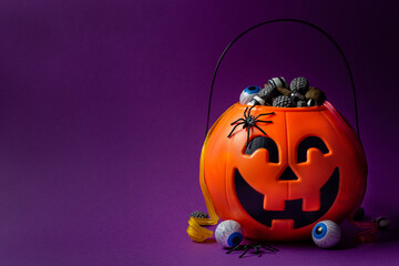 Jack-o-lantern bag full of candy on a purple background with copy space, horizontal