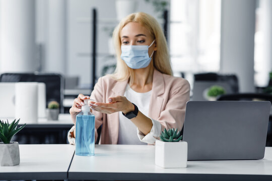 Safety and health protection at work in office. Millennial woman in protective mask with smart watch uses antiseptic at workplace with laptop for hand disinfection
