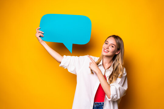Portrait of a happy young woman holding empty speech bubble standing over yellow background