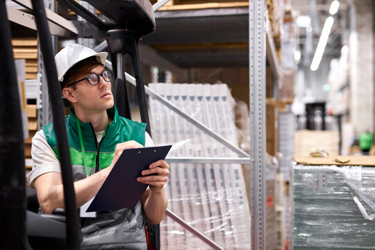 concentrated young warehouse worker in production department of modern store, take notes. export, logistics concept