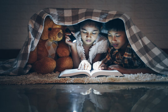 Happy children boy and girl reading a book in blanket at home with a toy teddy bear.