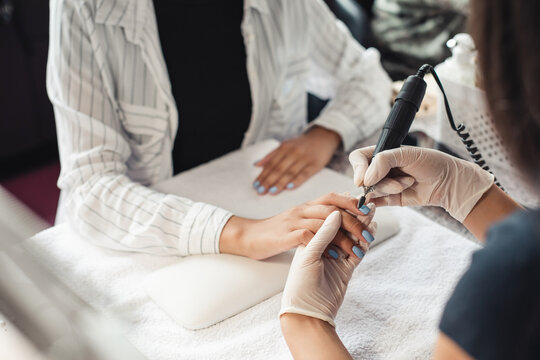 Beauty day and nail treatments. Professional manicure master in rubber gloves makes procedure removes varnish with an electric manicure device to african american client