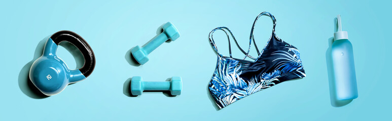 Fitness theme with dumbbells and a sportswear - flat lay