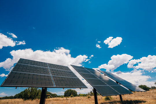 Solar panels in the desert with blue skies and puffy white clouds