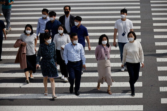 Pedestrians wearing masks walk on a zebra crossing amid the coronavirus disease (COVID-19) outbreak in Seoul, South Korea