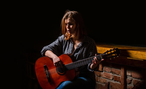 Girl play the guitar. Woman hipster man sitting in a pub. Woman playing guitar, holding an acoustic guitar in his hands. Music concept. Girl guitarist plays