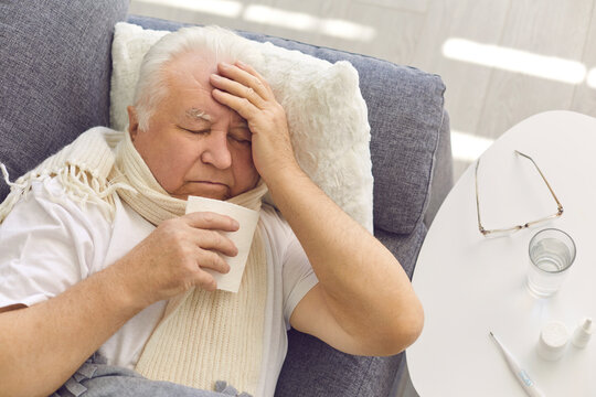 Senior man suffering from cold, flu or covid fever, coughing and having runny nose