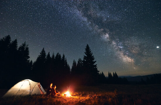 Side view of loving couple sitting near bright burning campfire and tent, enjoying beautiful camping night together under dark sky full of shiny stars and bright Milky Way, warm summer night.