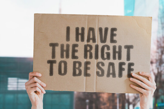 """The phrase """" I have the right to be safe """" on a banner in men's hand with blurred background. Safety. Security. Dangerous. Government. Protection. Privacy. Safeguard"""