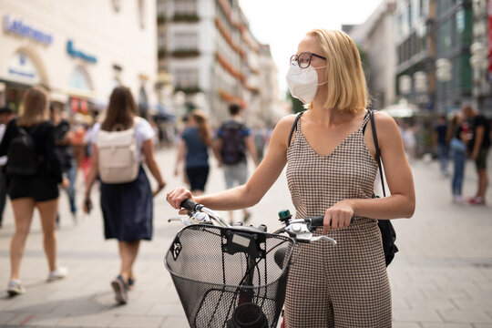 Woman walking by her bicycle on pedestrian city street wearing medical face mask in public to prevent spreading of corona virus. New normal during covid epidemic. Social responsibility.